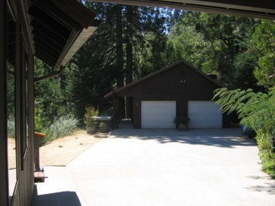 View of the garage and hot tub from the carport